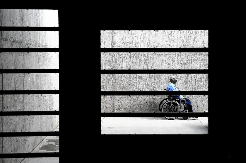 An inmate sits in a courtyard at the California Health Care Facility outside Stockton. A federal judge Tuesday ordered California to stop the practice of temporarily housing disabled inmates in isolation units while awaiting suitable cell assignments.