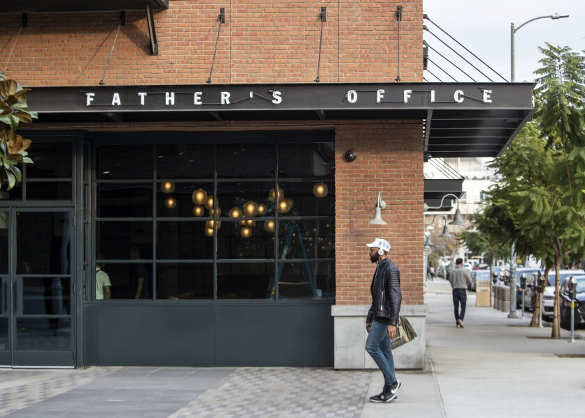 A man walks past the new Father's Office restaurant location in the Arts District.