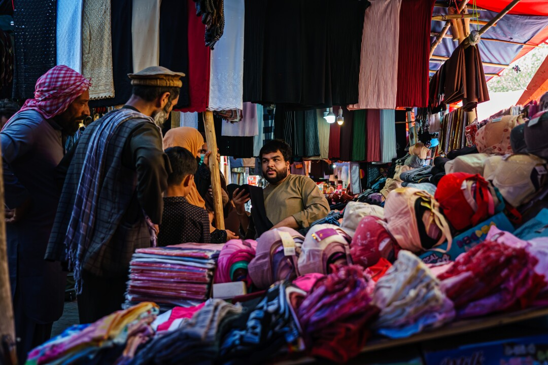 A shopkeeper talks to female and male customers