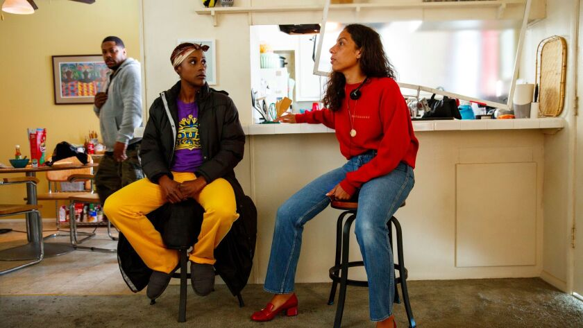 Issa Rae, in yellow pants, talks with executive producer Melina Matsoukas, in Rae's character's apar