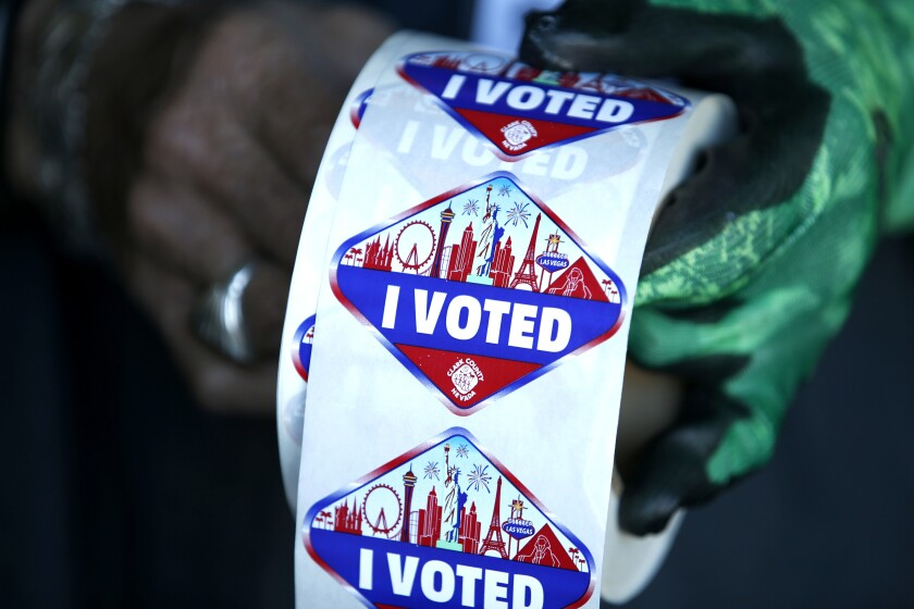 """FILE - In this Saturday, Oct. 17, 2020, file photo a poll worker displays """"I Voted"""" stickers during the first day of early voting in Las Vegas. Democrats have kept Nevada in their column in every presidential election since 2004. But political strategists and organizers on the ground warn Nevada is still a swing state. (Steve Marcus/Las Vegas Sun via AP, File)"""