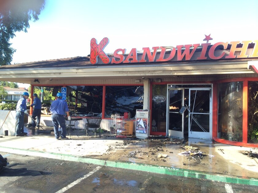 Contractors clean up after a nighttime fire destroyed K Sandwiches at Linda Vista Road and Mesa College Drive.