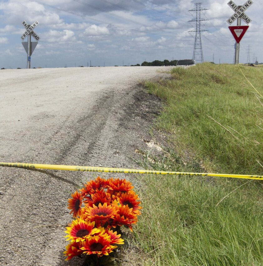Flowers sit next to police tape at the site of Saturday's hot air balloon crash near Lockhart, Texas, Sunday, July 31, 2016. A hot air balloon made contact with high-tension power lines before crashing into a pasture in Central Texas, killing all on board, according to federal authorities who are i