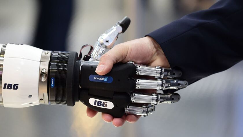 A person shakes hands with a robot during the Hanover Fair in Germany.