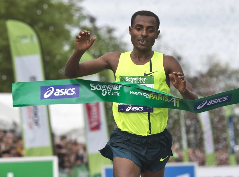 "FILE- In this Sunday, April 6, 2014 file photo, Ethiopia's runner Kenenisa Bekele crosses the finish line to win the 38th Paris Marathon,  in Paris. Bekele says his exclusion from Ethiopia's marathon team for the Olympics is ""unjust"" and has called the selection criteria the national federation use"