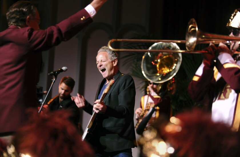 Fleetwood Mac's Lindsey Buckingham performs with the USC marching band at the university's Bovard Auditorium.