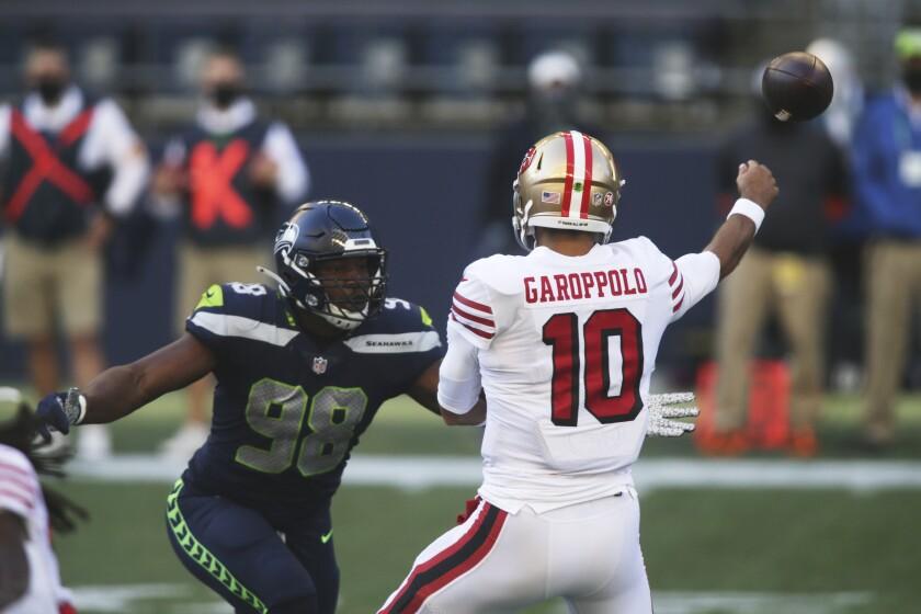 Seattle Seahawks defensive end Alton Robinson (98) pressures San Francisco 49ers quarterback Jimmy Garoppolo during the first half of an NFL football game, Sunday, Nov. 1, 2020, in Seattle. (AP Photo/Scott Eklund)
