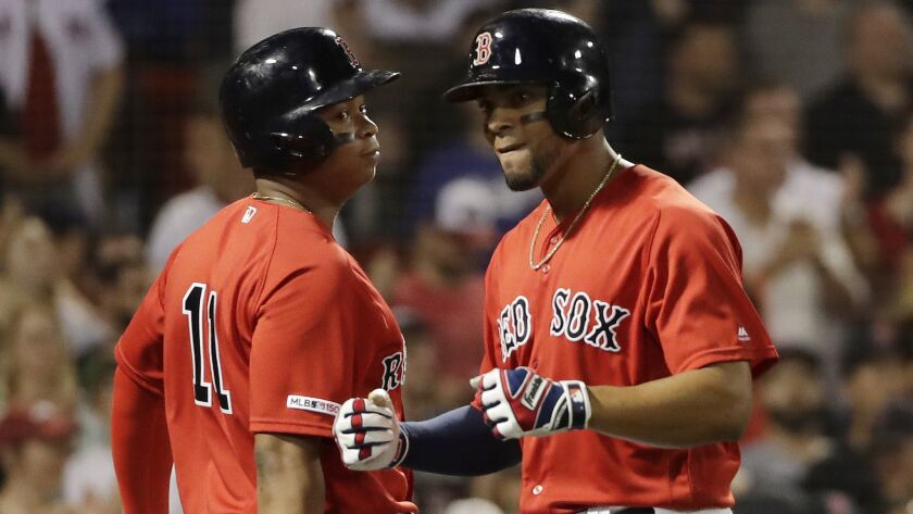 Boston Red Sox's Xander Bogaerts, right, celebrates his three-run home run with Rafael Devers during the seventh inning against the Dodgers on Friday in Boston.