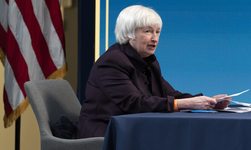 Yellen speaks while seated at a table, holding papers.