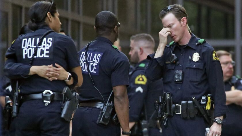 Dallas police officers wait outside the entrance of the emergency room at Texas Health Presbyterian Hospital Dallas following an April 24 shooting in which two officers were critically wounded.