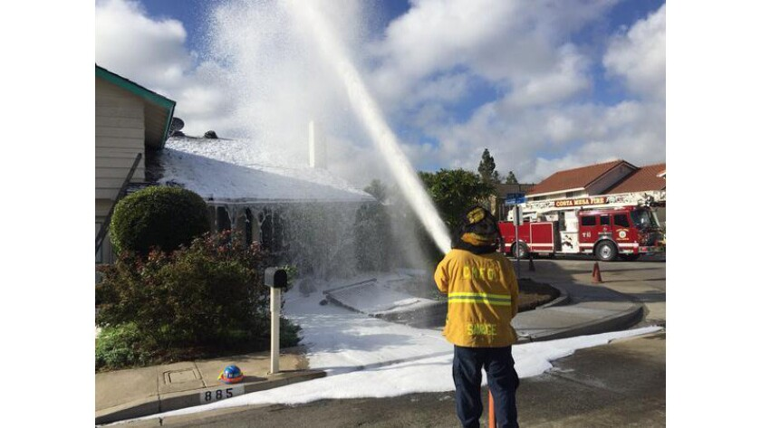A Costa Mesa firefighter sprays foam to calm a swarm of bees that stung a roofing worker 50 to 100 times on Thursday.