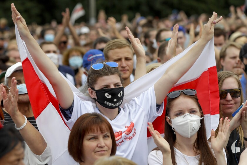 FILE - In this file photo taken on Sunday, July 19, 2020, Belarusians, some of them wearing face masks to protect against coronavirus, attend a meeting in support of Svetlana Tikhanovskaya, candidate for the presidential elections, in Minsk, Belarus. Previously apolitical, Kseniya Milya was among those who flocked to campaign rallies of Sviatlana Tsikhanouskaya, a 37-year old ex-teacher and wife of a jailed opposition blogger, who is challenging Lukashenko in Sunday's vote. (AP Photo/Sergei Grits)