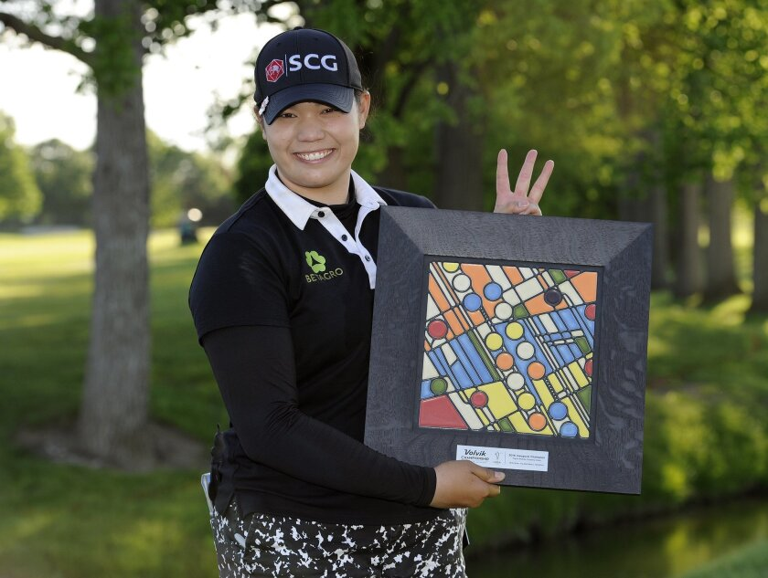 Ariya Jutanugarn, of Thailand, stands with the LPGA Volvik Championship trophy after winning the golf tournament at the Travis Pointe Country Club, Sunday, May 29, 2016 in Ann Arbor, Mich. Jutanugarn is holding up three fingers to signify that she has won three LPGA tournaments in a row. (AP Photo/Jose Juarez)