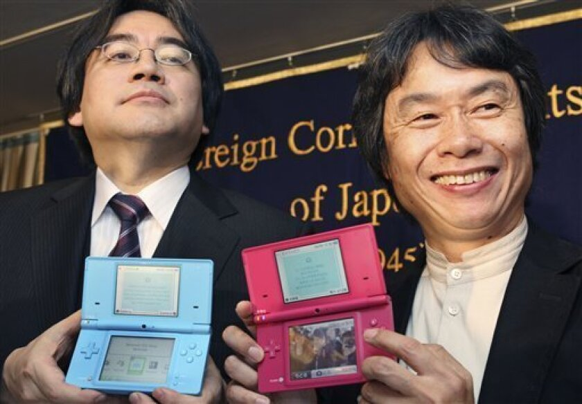 FILE - In this April 9, 2009 file photo, Nintendo Co. President Satoru Iwata, left, and Nintendo Senior Managing Director Shigeru Miyamoto pose for photographers with new Nintendo DSi handheld machines prior to their press conference in Tokyo Nintendo reported Thursday, May 7, 2009, an 8.5 percent rise in annual profit as the video game maker shrugged off the global slowdown that has battered other Japanese manufacturers. (AP Photo/Koji Sasahara, File)