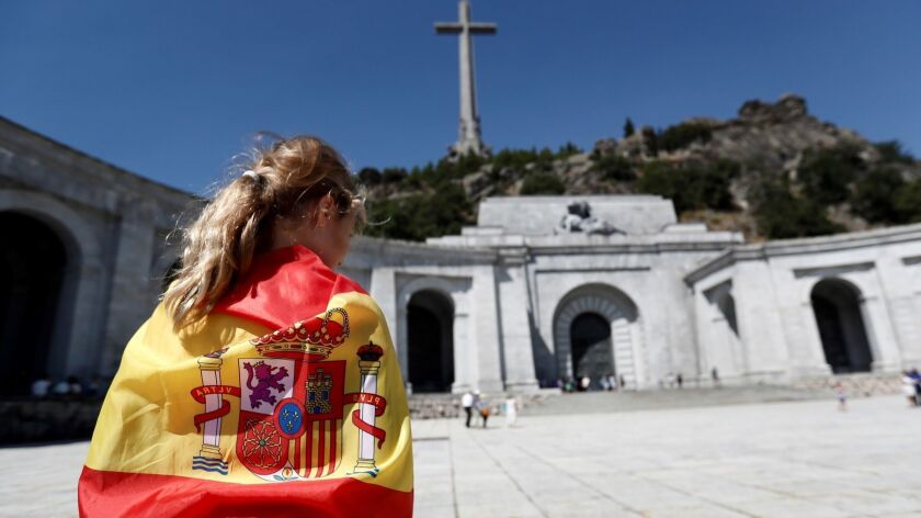 A woman wears the Spanish flag like a cape at the Valley of the Fallen memorial in San Lorenzo del Escorial.