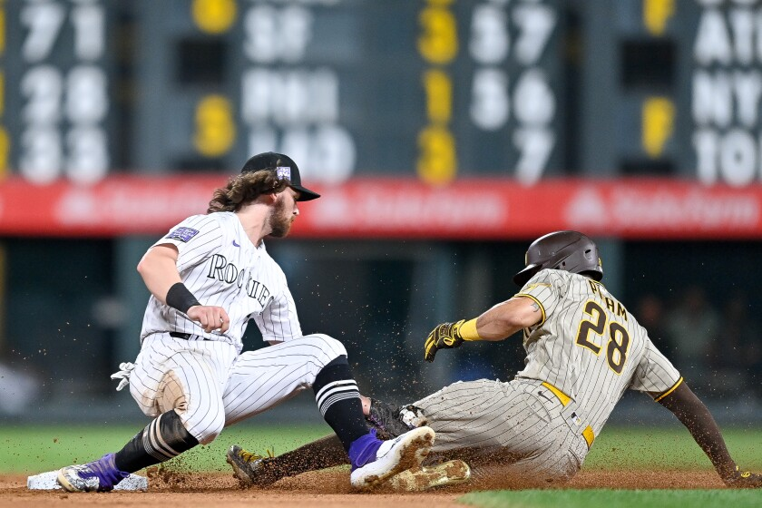 Padres' Tommy Pham is tagged out by Rockies' Brendan Rodgers attempting to steal second.