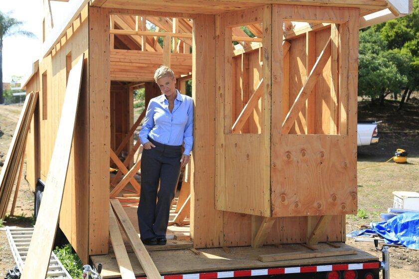 Janet Ashforth stands in what will be her front door once her tiny home of 300 square feet is completed. Ashforth plans to open a community of tiny homes in North County.