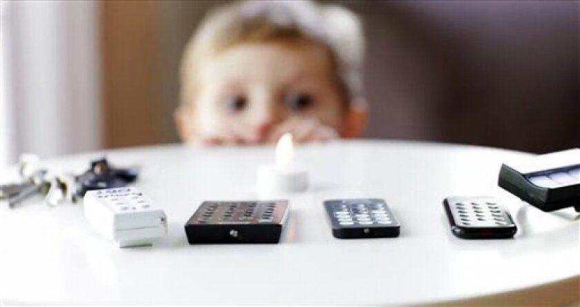 This frame grab provided Sept. 13, 2011, by Energizer/Safe Kids USA shows shows a youngster looks at remote controls that are powered by coin cell batteries. St. Louis-based Energizer, world's leading maker of so-called button batteries. is partnering with a child safety advocacy group to raise awareness of a growing problem: Children swallowing the small batteries. (AP Photo/Energizer/Safe Kids USA)