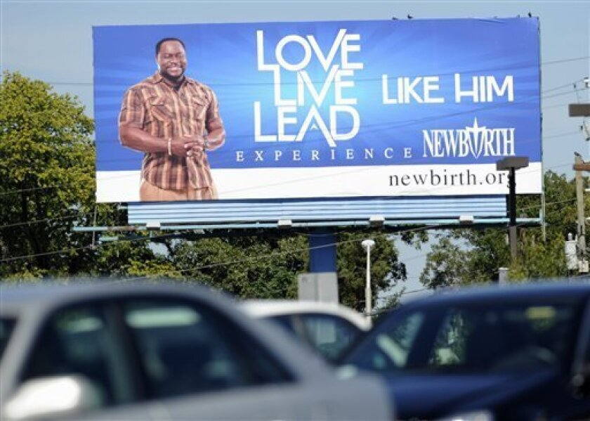 "In this Sept. 28, 2010 photo, traffic moves down a street as a billboard showing Bishop Eddie Long is seen above in Atlanta. The billboard near an Atlanta highway reads, ""Love Like Him, Live Like Him, Lead Like Him."" The motto refers to Jesus Christ, but the smiling face next to it is that of Bishop Eddie Long. (AP Photo/Mike Stewart)"