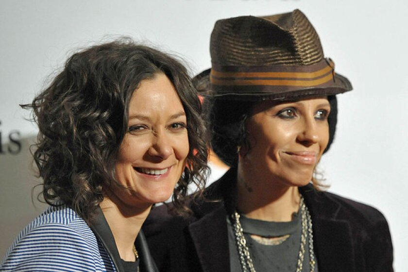 """Sara Gilbert, with girlfriend Linda Perry at Clive Davis' pre-Grammy party in February, announced their engagement Monday on """"The Talk."""""""
