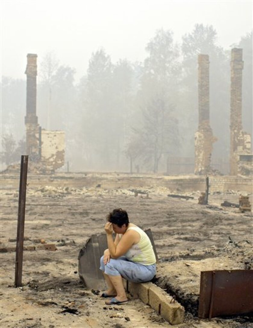 FILE - In this Aug. 7, 2010 file photo a woman sits amidst the charred chimneys, the remains of the houses after a spreading wildfire burned them to the ground as well as the entire village of Peredeltsy in Ryazan region, some 180 km (111 miles) southeast of Moscow, Russia. A devastating wave of wildfires across Russia could ravage millions of acres of forests and cause worse damage than last year's catastrophic blazes, environmentalists and officials said Thursday June 9, 2011. (AP Photo/Sergey Ponomarev, File)