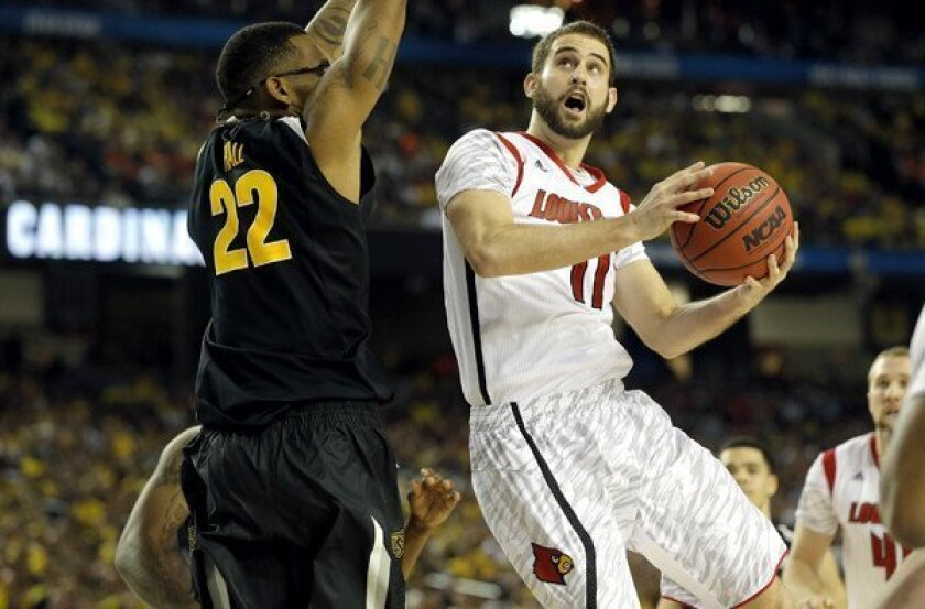 Louisville forward Luke Hancock drives to the basket against Wichita State forward Carl Hall (22) in the second half Saturday night at the Georgia Dome.