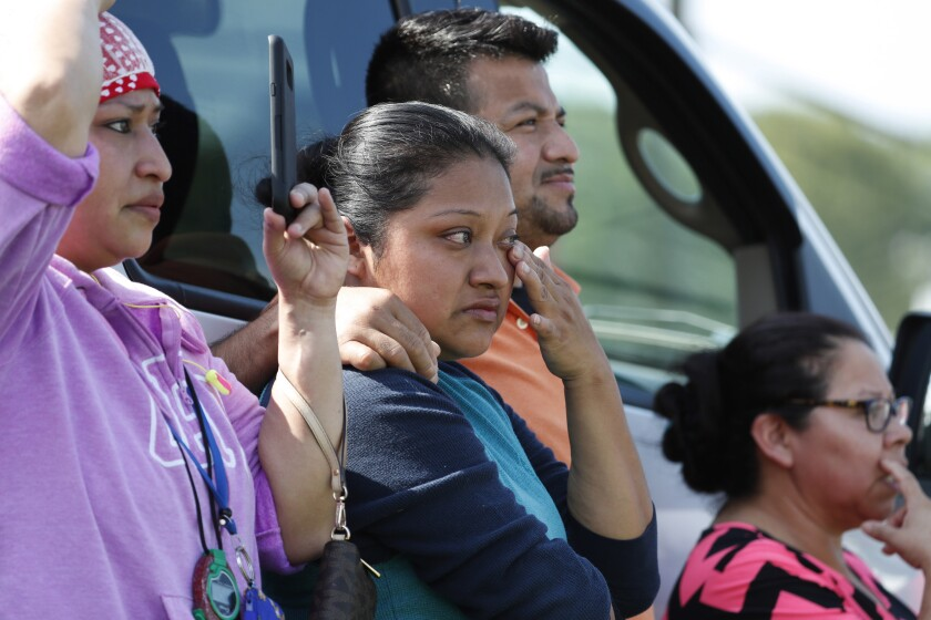 Family, friends and co-workers watch as immigration officials raid the Koch Foods plant.