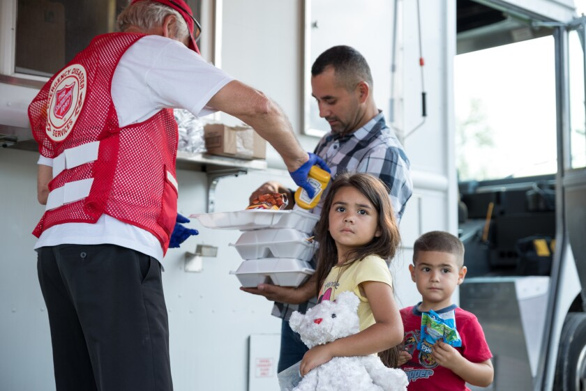 A Salvation Army volunteer provides meal to family in Houston