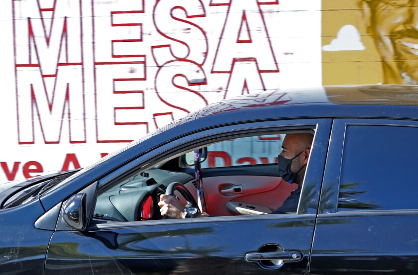 A man wears a face mask while driving on the 500 block of West 19th Street in Costa Mesa on Nov. 14.