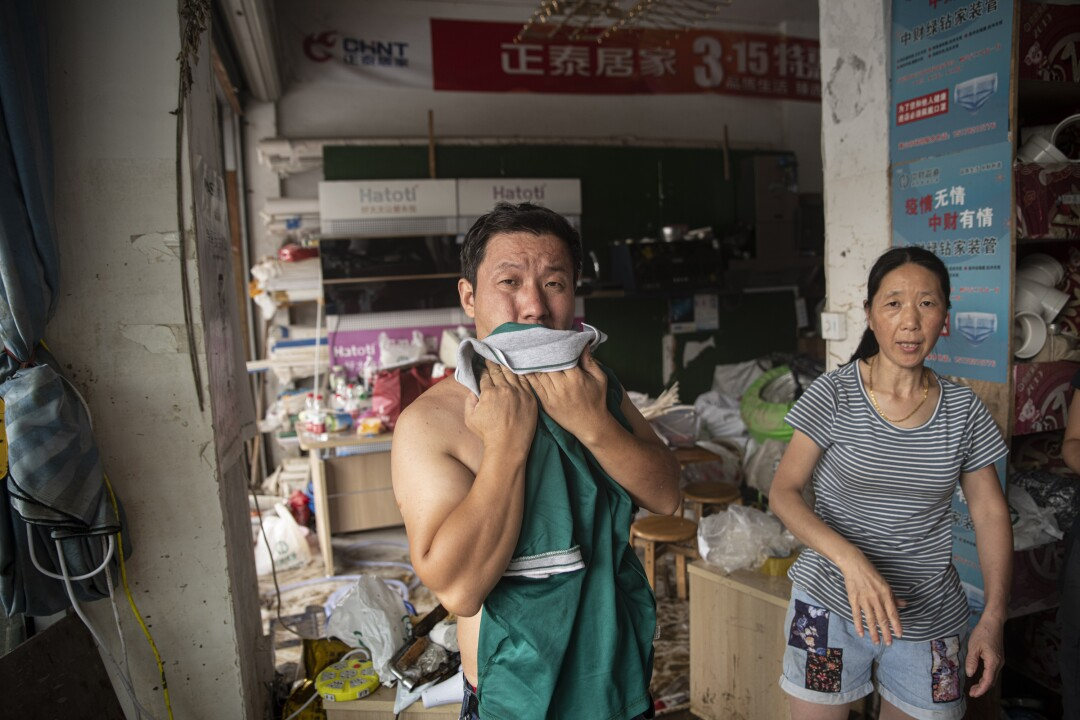 Members of the Shao family in Shexian, Anhui province, are still trying to clean up their store.