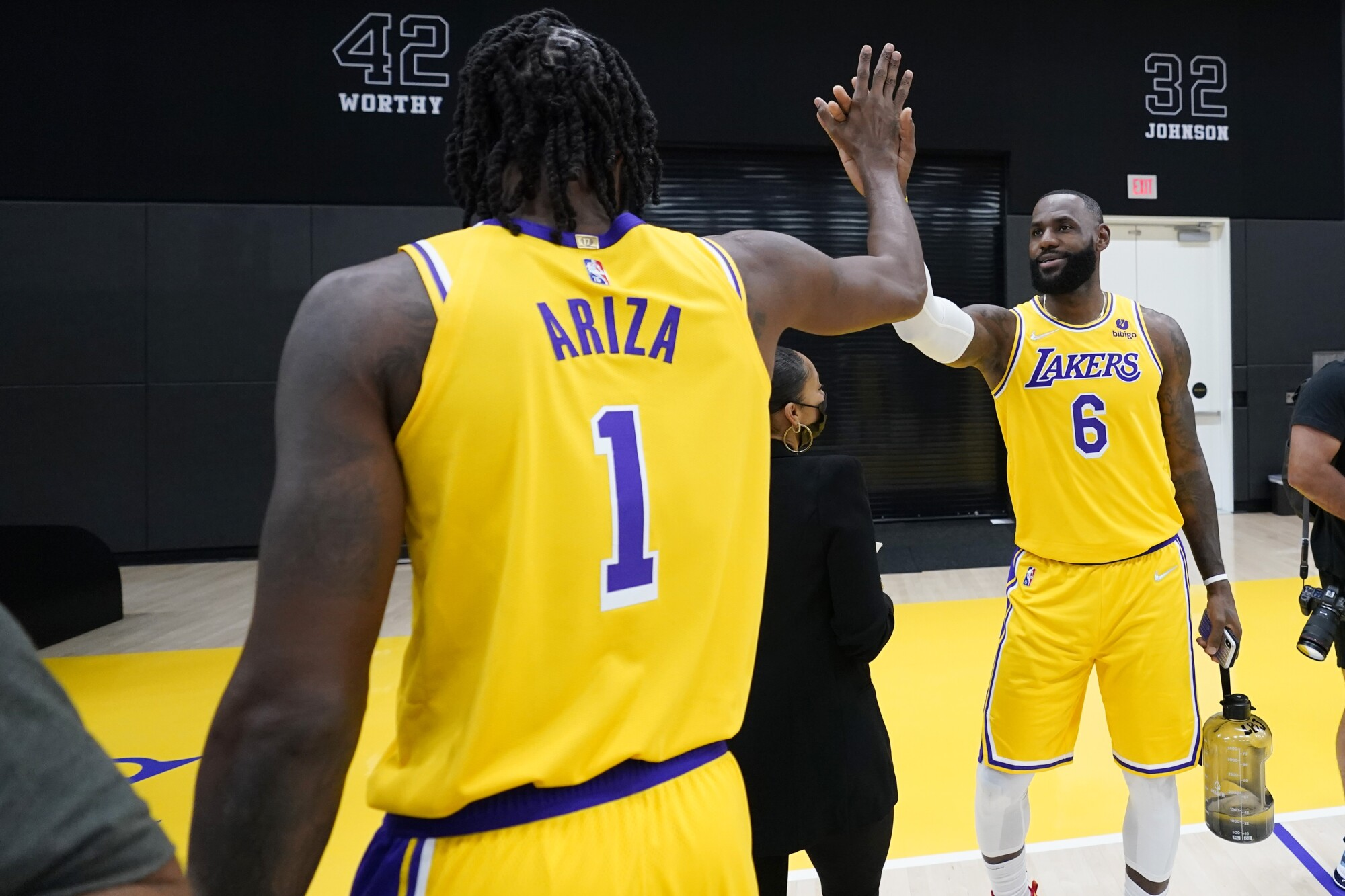 Los Angeles Lakers forward LeBron James, right, high-fives teammate Trevor Ariza.