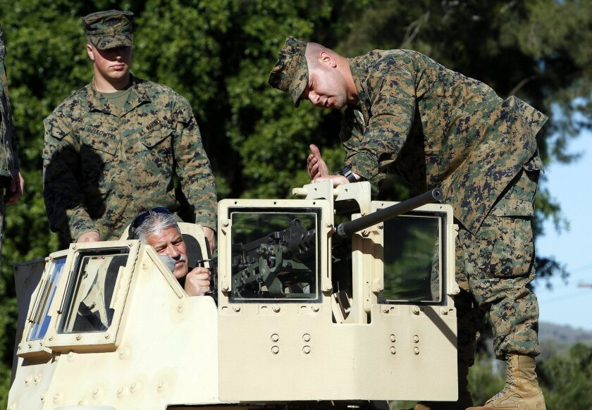 Marine Ln.Cp. Eric Dzikowski and Sgt. Stewart Carboni show off this .50 caliber M2  machine to veteran Tony Fuentes as he sat in the turret of an assault vehicle during a tour of Camp Pendleton with other veterans of the 1st Marine Division Association from several wars, from WWII to Afghanistan on