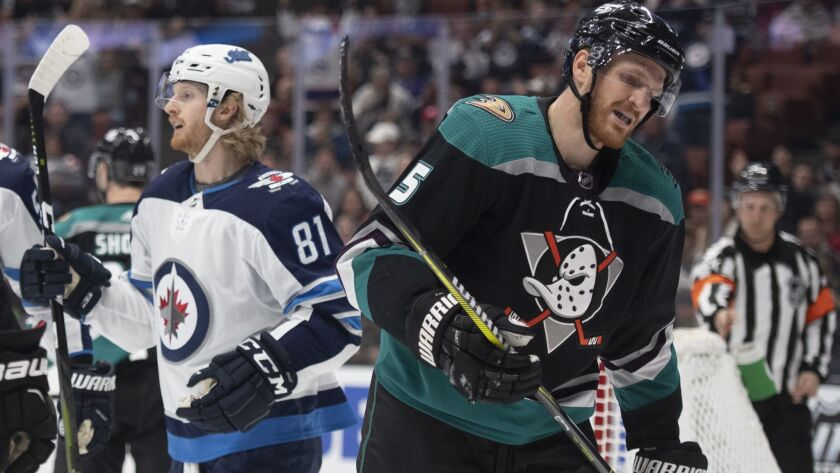 Anaheim Ducks defenseman Korbinian Holzer, right, reacts as Winnipeg Jets left wing Kyle Connor cele