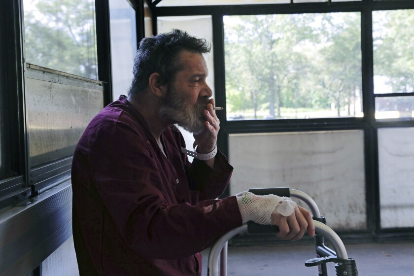 Patient Michael Swan rests his hand on his walker as he inhales a drag while taking a cigarette break in the smoking shack outside the West Roxbury campus of the Veterans Affairs Medical Center in Boston, Monday, Sept. 30, 2019. The VA is set to ban smoking at all its grounds nationwide starting Oct. 1, a welcome move by health-conscious veterans but not by others who enjoy a smoke between appointments. (AP Photo/Charles Krupa)