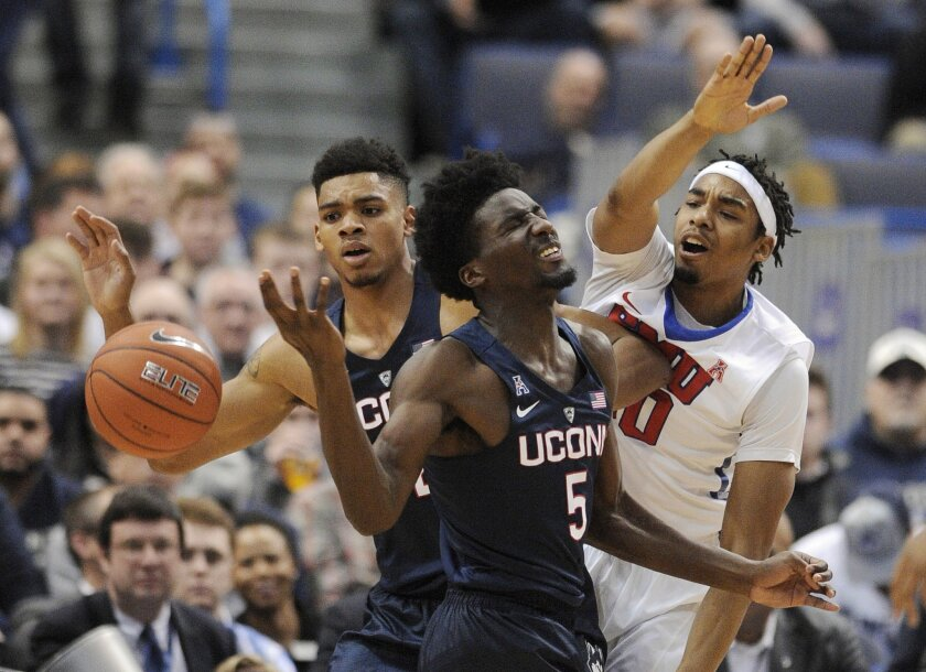 Connecticut's Daniel Hamilton (5) and Shonn Miller, left, fight for a loose ball with SMU's Ben Moore (00) during the first half of an NCAA college basketball game in Hartford, Conn., on Thursday, Feb. 18, 2016. (AP Photo/Fred Beckham)