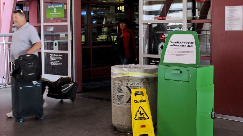 "Unidentified travelers exit the airport past a green metal container designed for ""Disposal for Pres"