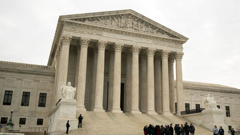 People wait outside the U.S. Supreme Court on Wednesday.