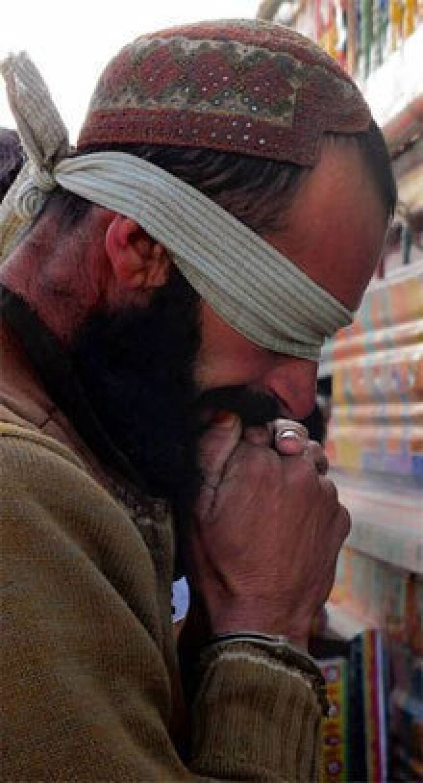 One of eight Taliban militants accused of smuggling bomb-making chemicals is presented to the news media in Ghazni, Afghanistan. At talks last week in France, Taliban representatives from Afghanistan said the militant group wasn't looking to monopolize power and would be willing to govern with other factions.