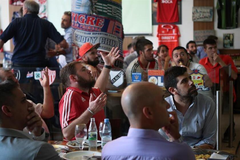 Hinchas de River Plate observan la transmisión por televisión del partido por las semifinales del Mundial de Clubes de la FIFA entre River Plate y Al Ain, que se disputa en Emiratos Árabes Unidos, hoy, en un bar de la ciudad de Buenos Aires (Argentina). EFE