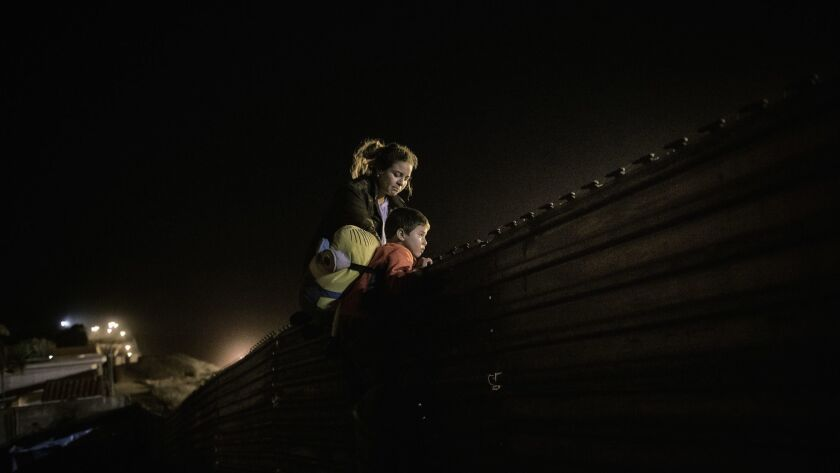 A migrant family from Honduras climbs the border fence to jump inside the United States to San Diego, from Tijuana, Mexico, Wednesday, Dec. 26, 2018.