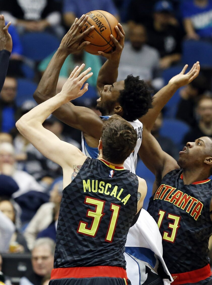 Minnesota Timberwolves' Andrew Wiggins, center, attempts a shot between Atlanta Hawks' Mike Muscala, left, and Lamar Patterson in the first quarter of an NBA basketball game, Wednesday, Nov. 25, 2015, in Minneapolis. (AP Photo/Jim Mone)