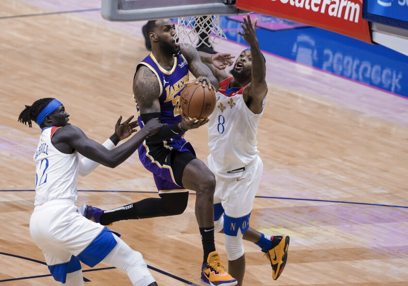 Lakers forward LeBron James drives to the basket against Pelicans forwards Wenyen Gabriel and Naji Marshall.