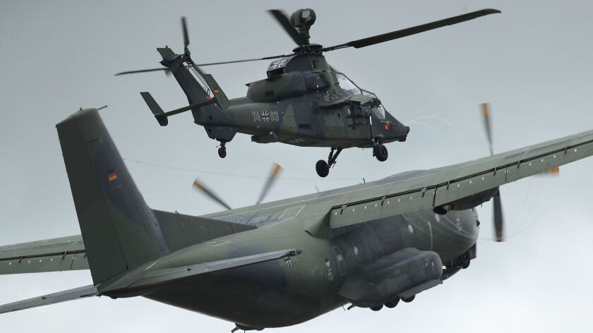 A Transall C-160 transport plane and a Eurocopter Tiger attack helicopter of the Bundeswehr, the German armed forces, participate in the ILA Berlin Air Show on April 25.