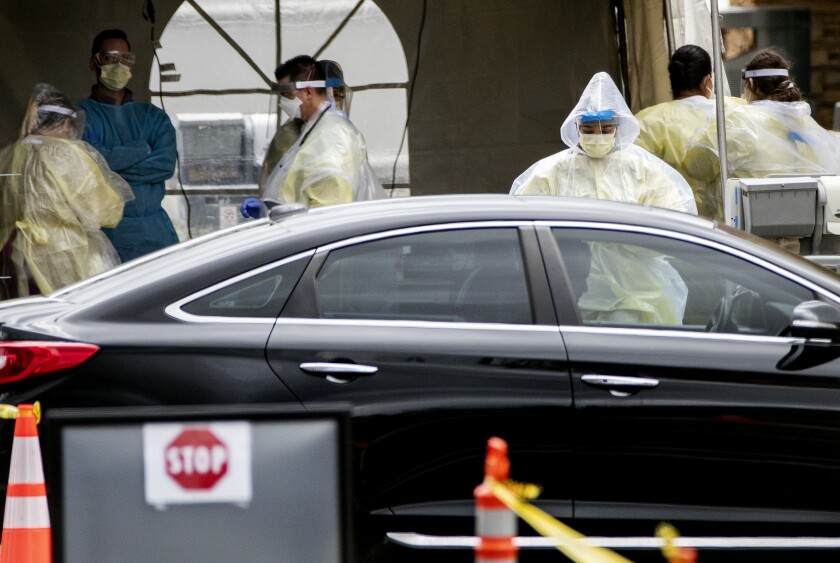 Medical personnel perform coronavirus tests at a drive-through site at St. Jude Heritage Medical Group in Yorba Linda