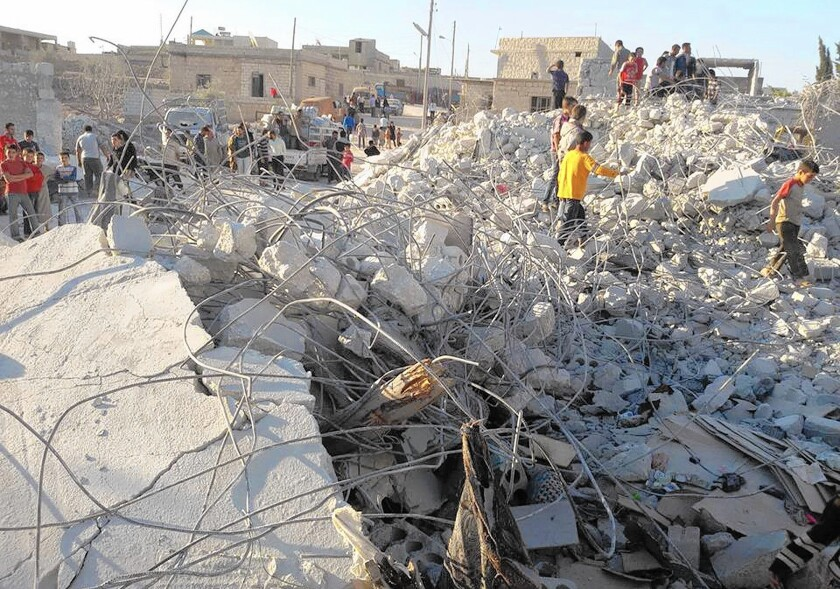 Syrians check a damaged house they say was targeted in U.S.-led airstrikes Sept. 23 in the village of Kfar Derian, a base for the Al Qaeda-linked Nusra Front.