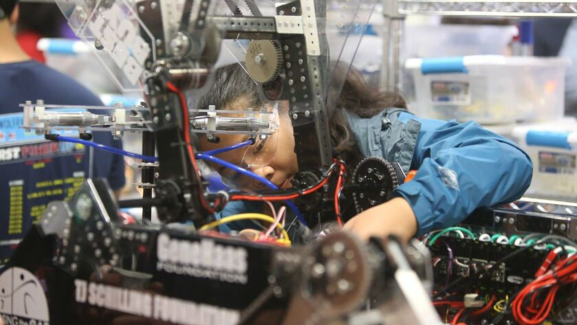 Athena Wilson from team Wolfpack Robotics makes final adjustments on her mechanical robot as she com