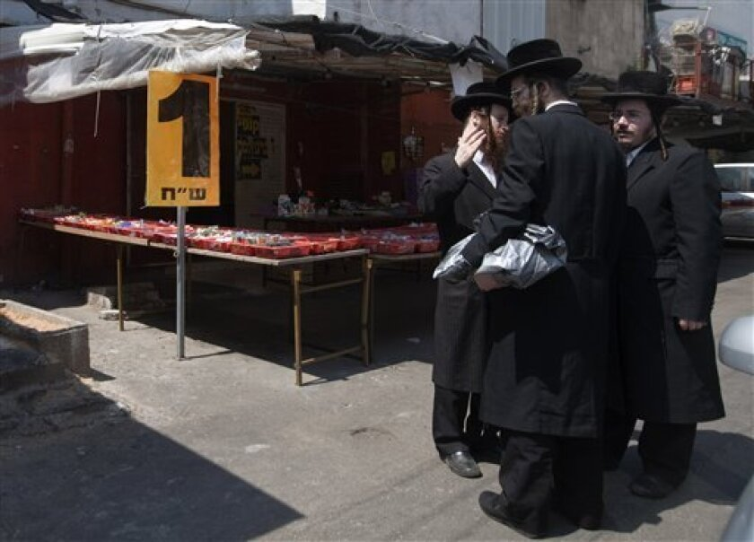 In this May 3, 2010 photo an Ultra Orthodox Jewish men stand near a sweets stall in Bnei Brak near Tel Aviv, Israel. Israel's ultra-Orthodox community, which has traditionally used violent protests and political clout to push its agenda, is turning to a new tactic to get its way in this overwhelmingly secular society: market power. (AP Photo/Dan Balilty)