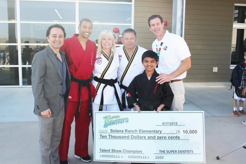 Contest winner Aarav Chandra, second from right, with, L-R,Super Dentists' Dr. Kami Hoss, Church's ATA Martial Arts instructors Ciel Solwazi, Patricia Church, and Senior Master Ken Church, and Solana Ranch Principal Jerry Jones.