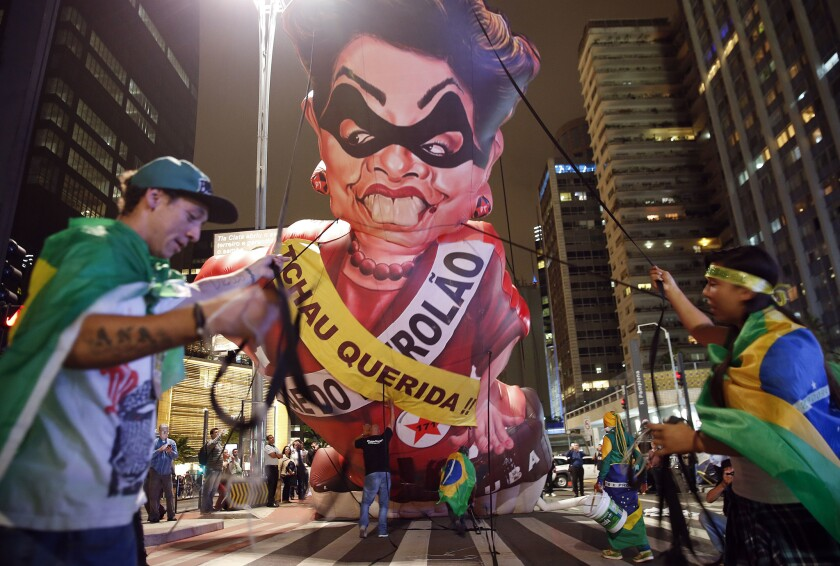 """Demonstrators set up an inflatable caricature of Brazil's President Dilma Rousseff wearing sashes reading """"Goodbye dear"""" and """"Mother of Big Oil"""" in Portuguese in Sao Paulo on May 11."""