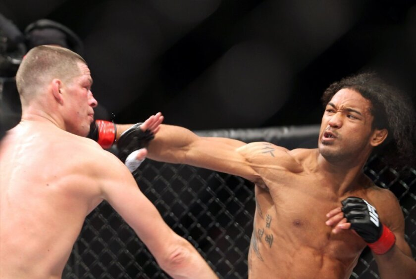 Nate Diaz, left, gets hit by Benson Henderson on Saturday.